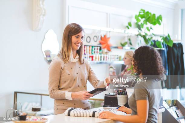 customer purchasing items at an upscale fashion boutique - jewellery products stock photos and pictures