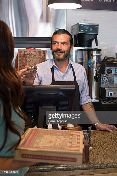 Customer purchasing pizza in cafe
