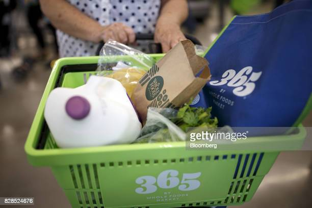A customer pushes a basket of groceries during the grand opening of a Whole Foods Market 365 location in Santa Monica California US on Wednesday Aug...