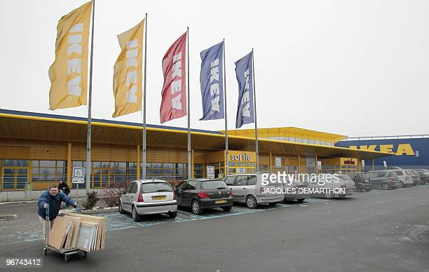 A customer pushes a cart in front of the Ikea store in RoissyenFrance north of Paris as workers of the Swedish furniture designer Ikea hold a...