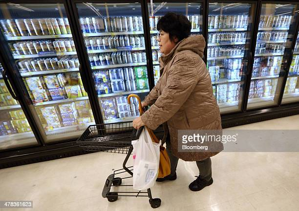 A customer pushes a cart in past a refrigerator containing cans of beer in a Seiyu GK supermarket a discount chain owned by WalMart Stores Inc in...