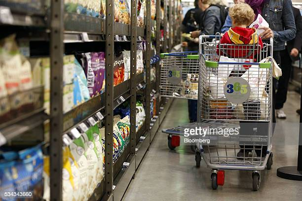 A customer pushes a cart while shopping on the opening day of the 365 by Whole Foods Market store in the Silver Lake neighborhood of Los Angeles...