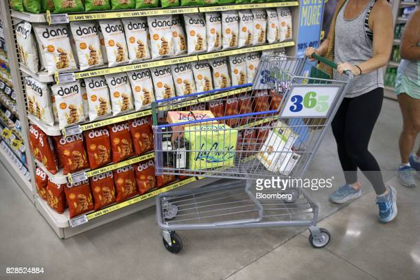 A customer pushes a cart with cases of LaCroix sparking water while shopping during the grand opening of a Whole Foods Market 365 location in Santa...
