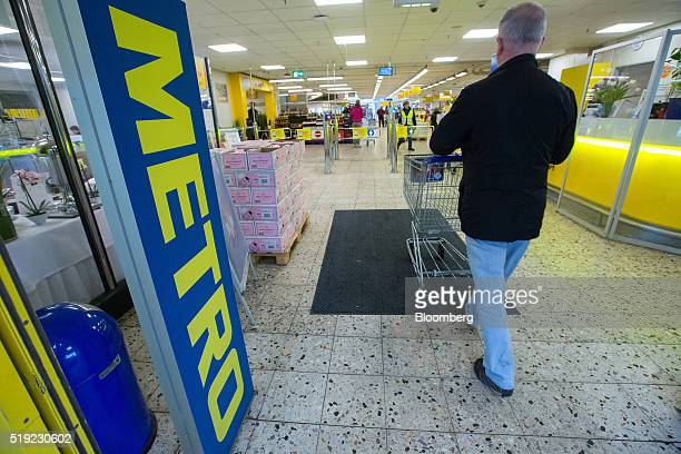 A customer pushes a shopping cart as they enter a Metro AG Cash Carry wholesale store in Duesseldorf Germany on Tuesday April 5 2016 German retailer...