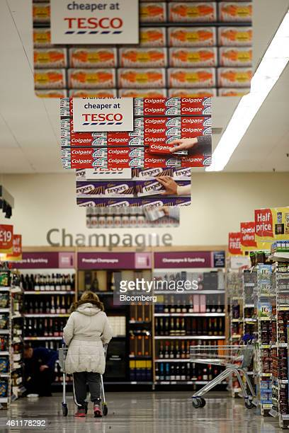 A customer pushes a shopping cart beneath posters reading 'Cheaper at Tesco' as she walks towards the beers wines and spirits section inside a Tesco...