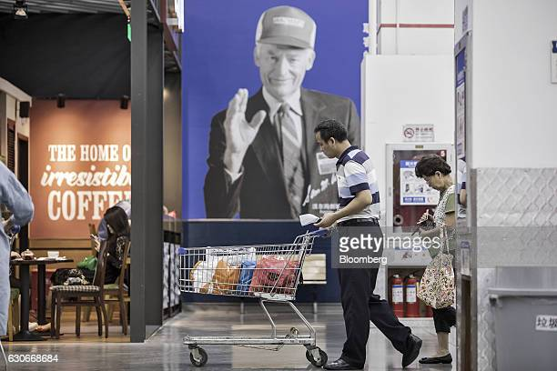 A customer pushes a shopping cart in front of an advertisement featuring the photograph of WalMart Stores Inc founder Sam Walton at the company's...