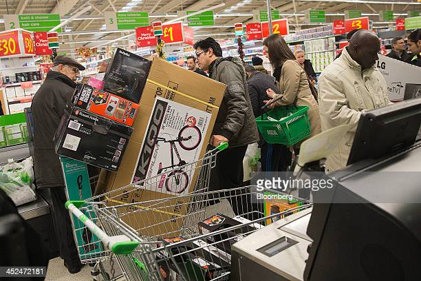 A customer pushes a shopping cart loaded with electronic goods and a bicycle through the selfserve check out desks during a Black Friday discount...
