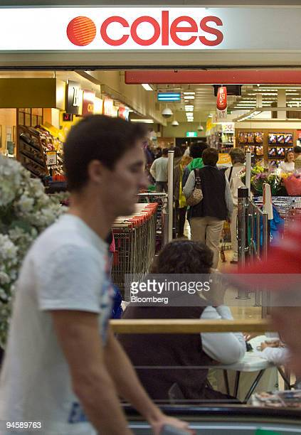 A customer pushes a shopping cart out of a Coles Group Ltd supermarket in Sydney Australia on Saturday July 7 2007 Wesfarmers Ltd whose takeover of...