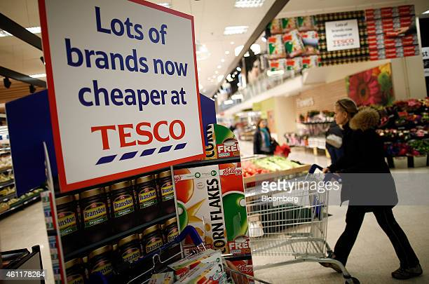 A customer pushes a shopping cart past a poster reading 'Lots of brands now cheaper at Tesco' inside a Tesco supermarket store operated by Tesco Plc...