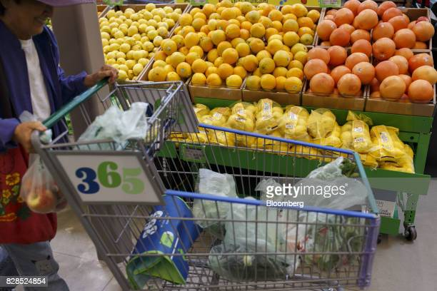 A customer pushes a shopping cart past produce during the grand opening of a Whole Foods Market 365 location in Santa Monica California US on...