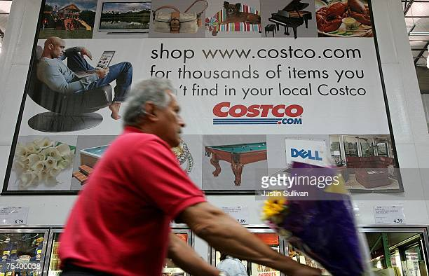 A customer pushes a shopping cart through a Costco warehouse store July 13 2007 in Richmond California Costco Wholesale Corporation reported a six...