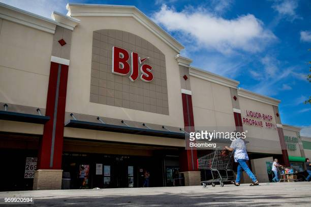 A customer pushes a shopping cart towards the entrance of a BJ's Wholesale Club Holdings Inc location in Miami Florida US on Friday May 18 2018 The...