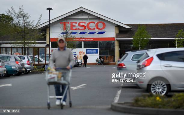 A customer pushes a shopping trolley as he walks through the car park of a Tesco store in Sevenoaks southeast of London on April 12 2017 Supermarket...