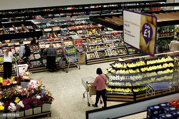 A customer pushes her shopping cart past a display of bananas in the fruit and vegetable section of a Tesco Extra Supermarket operated by Tesco Plc...