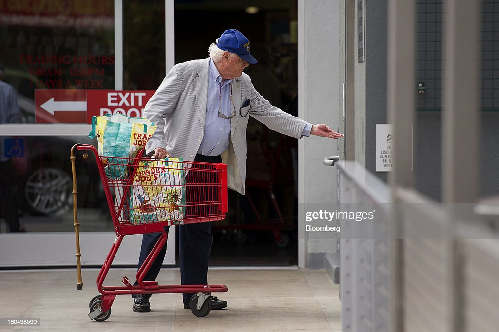 A customer pushes the call button for the parking garage lift as he leaves a Trader Joe's Co. store in San Francisco, California, U.S., on Friday, Sept. 13, 2013. Trader Joe's Co., the closely held grocery store chain, will end health benefits for part-time workers next year, directing them instead to anew insurance marketplaces as companies revamp medical coverage to fit the U.S. Affordable Care Act. Photographer: David Paul Morris/Bloomberg via Getty Images