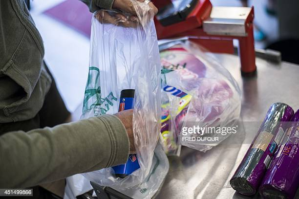 A customer puts groceries in a plastic bag on June 30 2014 in a supermarket in Paris A governmental amendment added to the biodiversity bill on June...