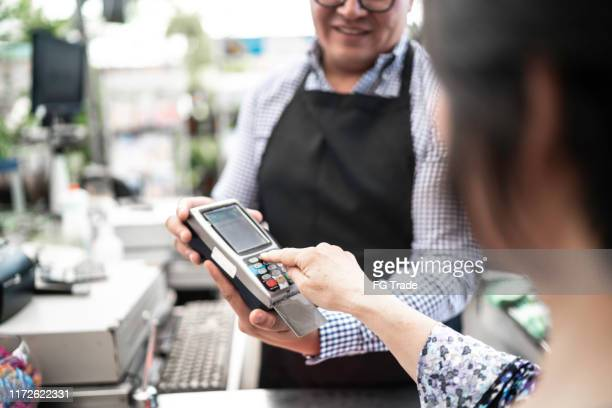 customer putting the password at credit card payment on checkout counter at small business - inserting stock pictures, royalty-free photos & images