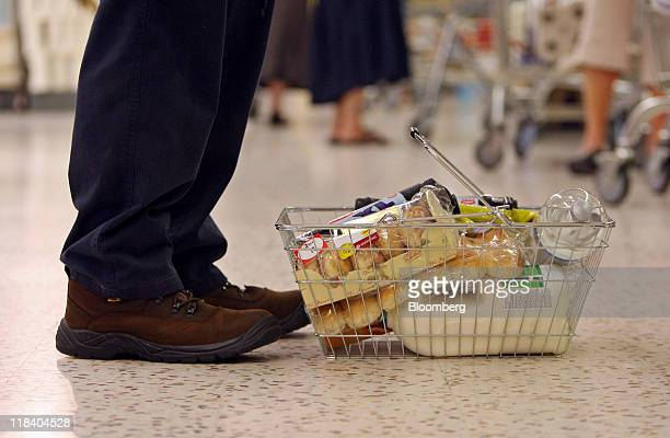 A customer queues at the checkout area with a basket of groceries at a Morrisons supermarket in Canvey Island UK on Thursday July 7 2011 William...