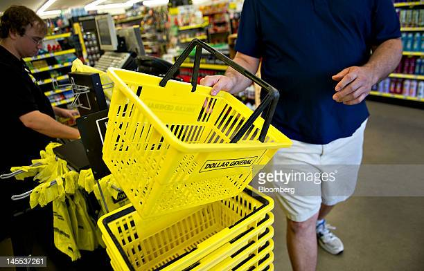 Customer Ray Knotts returns a shopping basket while checking out at a Dollar General Corp store in Creve Coeur Illinois US on Thursday May 31 2012 US...