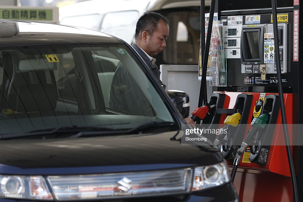 A customer reaches for a fuel pump at a self gas station in Soka City, Saitama Prefecture, Japan, on Friday, Jan. 25, 2013. Japan's consumer prices fell for the seventh time in eight months, underscoring the risk that the central bank may struggle to reach a 2 percent inflation target unless it implements new easing measures earlier than planned. Photographer: Kiyoshi Ota/Bloomberg via Getty Images
