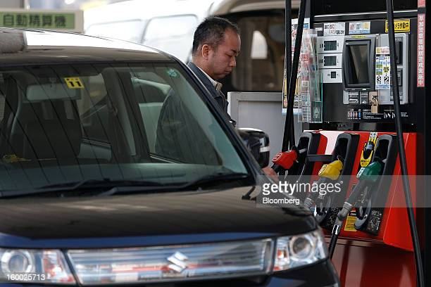 A customer reaches for a fuel pump at a self gas station in Soka City Saitama Prefecture Japan on Friday Jan 25 2013 Japan's consumer prices fell for...
