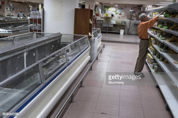 A customer reaches for bread on near empty shelves at a grocery store in Caracas Venezuela on Tuesday Jan 9 2018 Hordes of desperate shoppers emptied...
