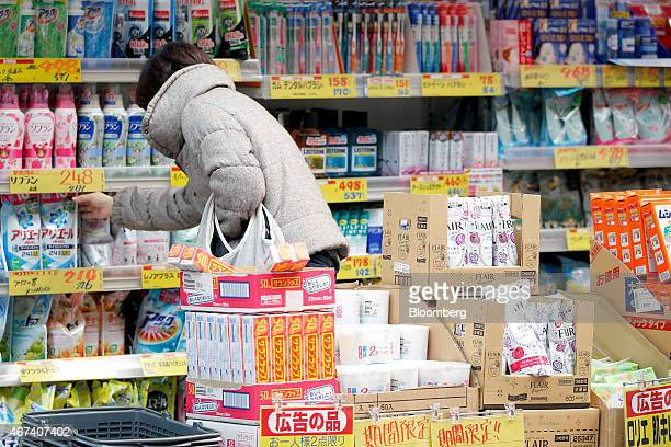 A customer reaches for laundry detergent at a drugstore in a shopping arcade in Tokyo Japan on Monday March 23 2015 Bank of Japan Governor Haruhiko...