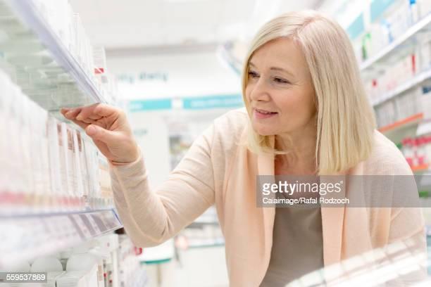Customer reaching for box on shelf in pharmacy