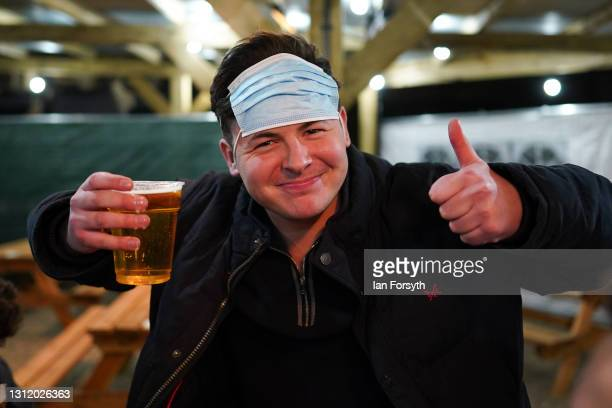 Customer reacts as he enjoys a drink at the Switch bar in Newcastle shortly after midnight following the easing of lockdown measures on April 12,...
