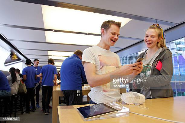 A customer reacts as he tries the iPhone 6 at the Apple Inc George Street store during the sales launch of the iPhone 6 and iPhone 6 Plus in Sydney...