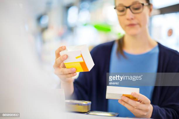 Customer reading label on medicine box in store