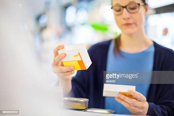Customer reading label on medicine box in store