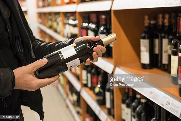 Customer reading label on red wine bottle in a supermarket, Munich, Bavaria, Germany