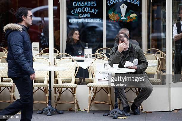 A customer reads a book at a cafe in Paris France on Saturday Nov 14 2015 French President Francois Hollande blamed Islamic State militants for...