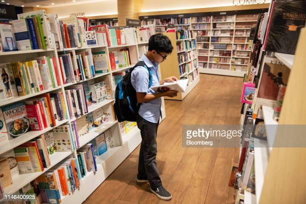 A customer reads a book in the Kinokuniya Co book store at the Aeon Mall in Phnom Penh Cambodia Sunday May 26 2019 Kinokuniya Japan's largest...