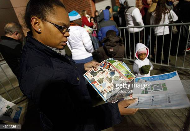A customer reads a WalMart sales circular as she waits in line to enter the store Thanksgiving day on November 28 2013 in Troy Michigan Black Friday...