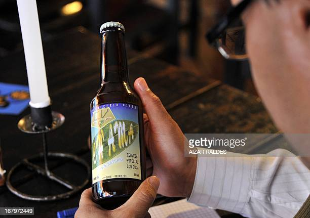 A customer reads the label of a bottle of Ch'ama a coca leaves and barley based beer in a bar in La Paz on May 2 2013 The beer made with organic...