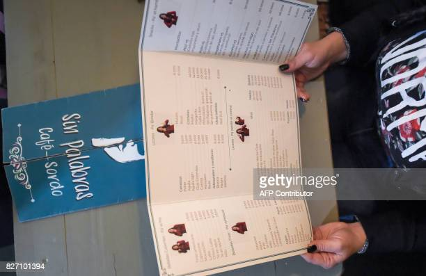 A customer reads the menu at the 'Sin Palabras' coffee bar in Bogota on July 19 2017 With menus with vignettes depicting sign language lamps to call...