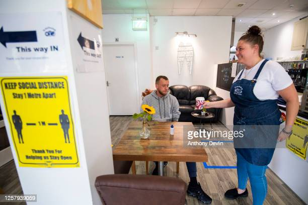 A customer receives a drink in the Hideaway Lounge Coffee Shop on July 24 2020 in Manchester England From today consumers in the United Kingdom must...