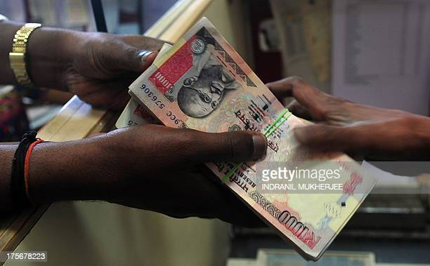 A customer receives a wad of Indian rupee notes from a foreign exchange dealer in Mumbai on August 6 2013 India's rupee plunged to a fresh record low...