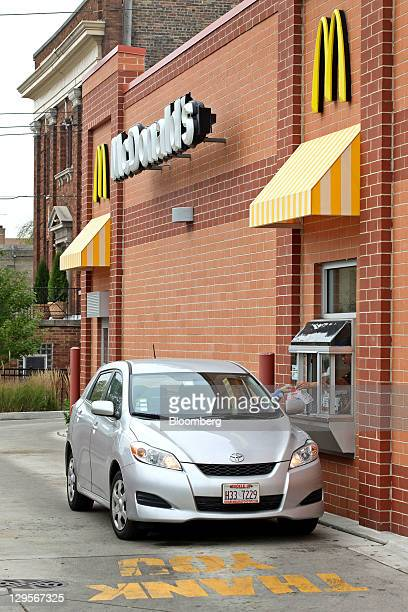 A customer receives an order at the driveup window of a McDonald's Corp restaurant in Chicago Illinois US on Tuesday Oct 18 2011 McDonald's Corp is...