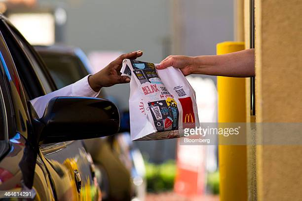 A customer receives an order from an employee at the drivethru of a McDonald's Corp restaurant in San Pablo California US on Wednesday Jan 22 2014...