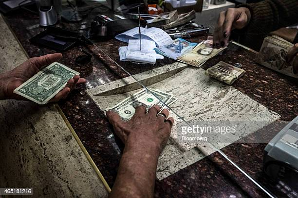 A customer receives US dollars during a transaction at an Italcambio currency exchange house in Caracas Venezuela on Tuesday Feb 24 2015 Venezuela...