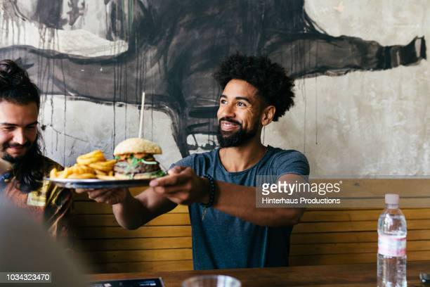 customer receiving food at burger restaurant - restaurant stock pictures, royalty-free photos & images