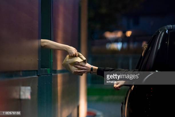 customer receiving food at drive thru - food delivery foto e immagini stock