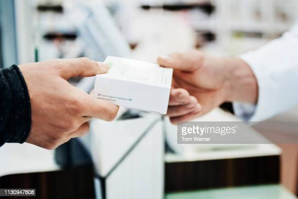 a customer receiving his prescription from pharmacy - 渡す ストックフォトと画像