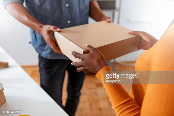 customer receiving the parcel from delivery man - receiving stock pictures, royalty-free photos & images