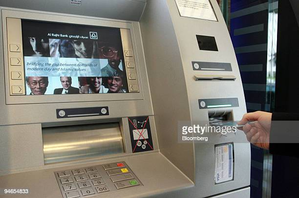A customer relations officer demonstrates how to use an ATM at the Al Rajhi Bank in Kuala Lumpur Malaysia on Monday Feb 5 2007