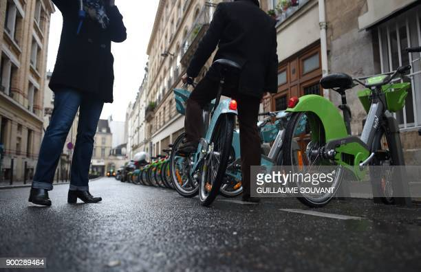 A customer rides away on the blue coloured electricmodel of Paris' new Velib bicyclesharing service operated by FrancoSpanish consortium Smovengo at...