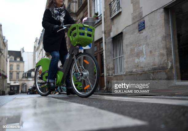 A customer rides on the green coloured manual model of Paris' new Velib bicyclesharing service operated by FrancoSpanish consortium Smovengo at a...